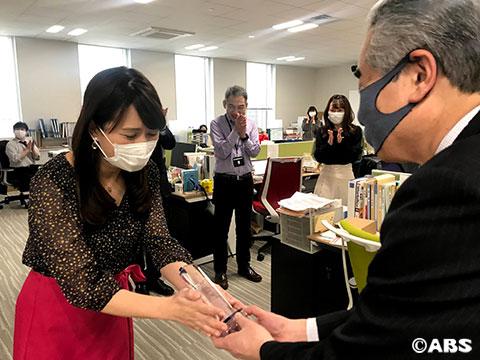 立田聡社長からトロフィーを受け取る酒井アナ